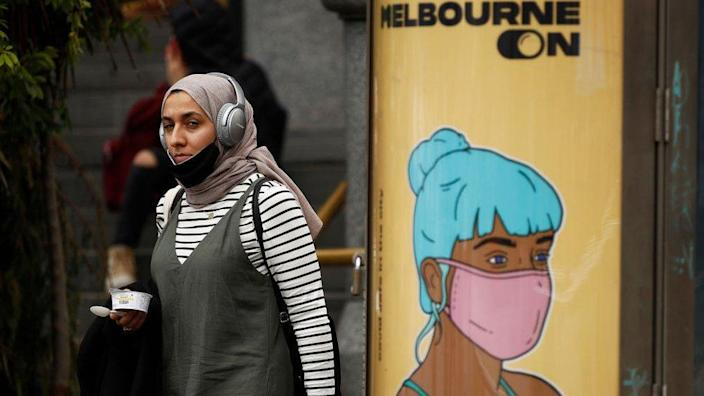 A young woman wearing a mask and a hijab walks past a pole with an ad featuring a graphic illustration of a woman with blue hair wearing a mask