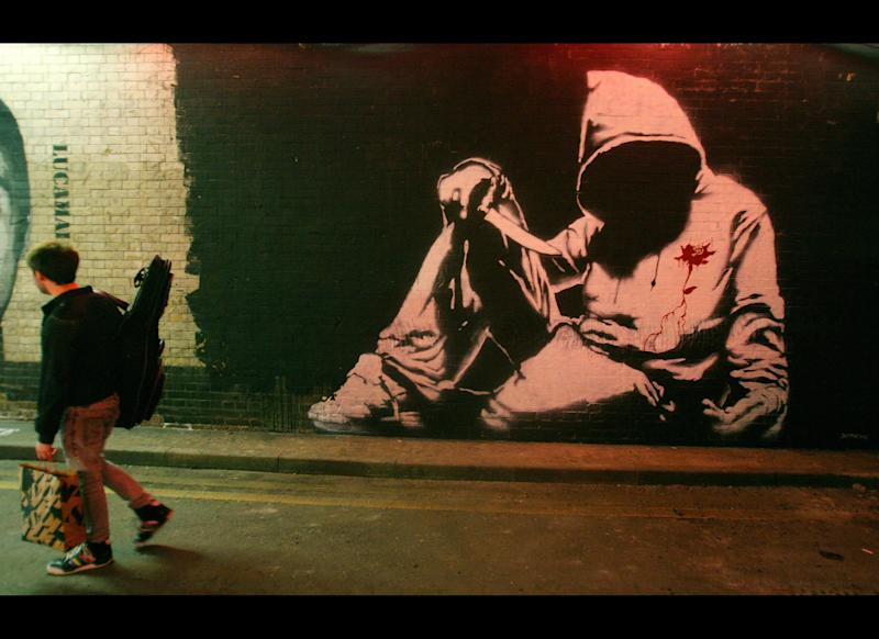 A man walks past a Banksy graffiti artwork during 'Cans' graffiti exhibition in London, on May 3, 2008. British artist Banksy and other graffiti artists have contributed to the free exhibition which has been painted onto the walls of a public London street. AFP PHOTO/CARL DE SOUZA (Photo credit should read CARL DE SOUZA/AFP/Getty Images)