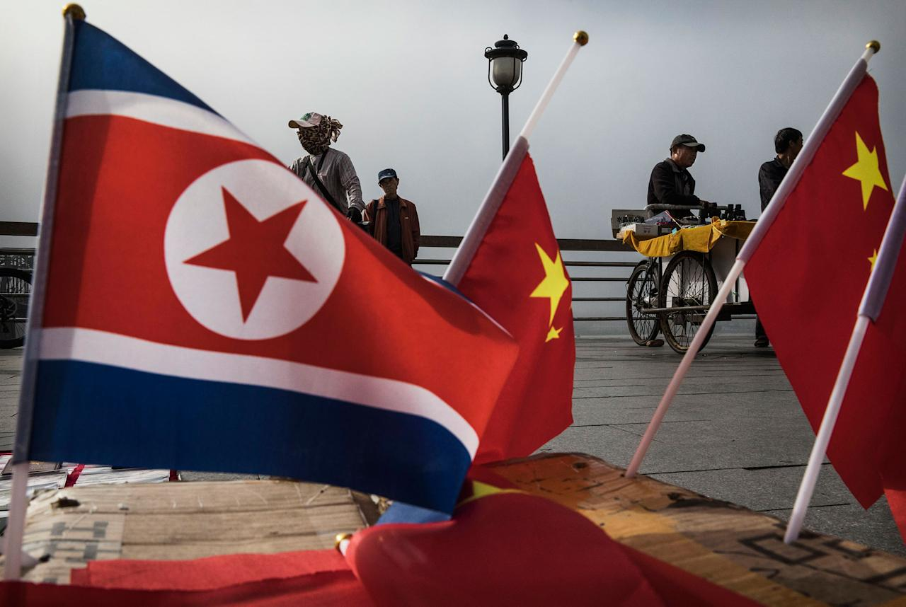 <p>Chinese vendors sell North Korea and China flags on the boardwalk next to the Yalu river in the border city of Dandong, Liaoning province, northern China across from the city of Sinuiju, North Korea on May 24, 2017 in Dandong, China. (Photo: Kevin Frayer/Getty Images) </p>