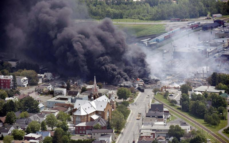FILE - In this July 6, 2013, file photo, smoke rises from railway cars from now-defunct Montreal, Maine & Atlantic Railways company that were carrying crude oil after derailing in downtown Lac Megantic, Quebec, Canada. Attorneys general for North Dakota and Montana have petitioned the Trump administration to overrule a Washington state law that imposes safety restrictions on oil shipped by rail from the Northern Plains. Montana Attorney General Tim Fox and North Dakota's Wayne Stenehjem say in a Wednesday, July 17, 2019, petition that federal authority over railroads should pre-empt the state law. (Paul Chiasson/The Canadian Press via AP, File)