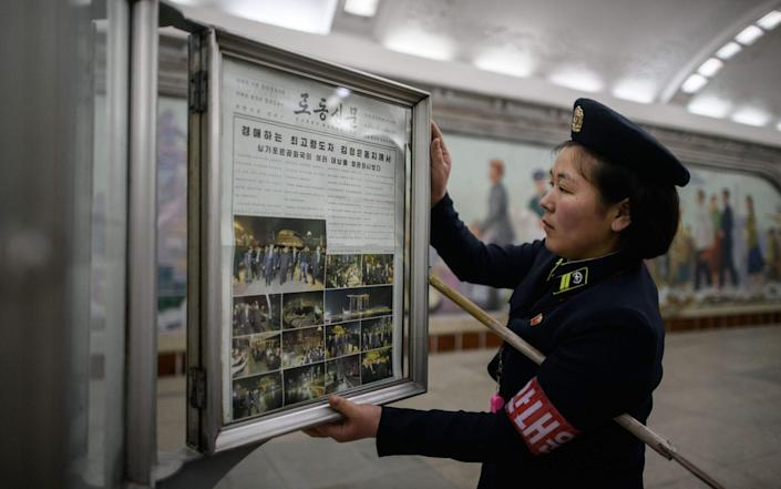A conductor changes the Rodong Sinmun newspaper showing images of North Korean leader Kim Jong Un in Singapore ahead of his meeting - AFP