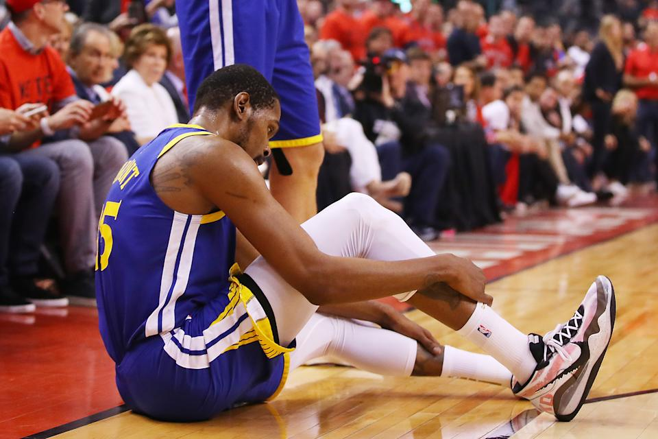 Kevin Durant clutched his lower right leg and had to be helped off the court after suffering an apparent lower-leg injury. (Getty)