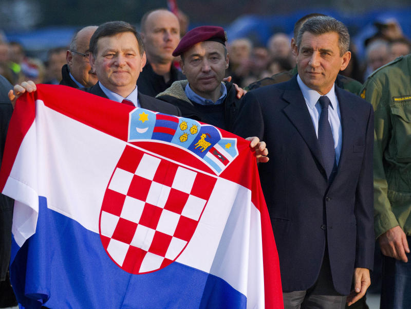 Croatian Gen. Ante Gotovina, right and Gen. Mladen Markac hold the Croatian flag upon their arrival to the airport in Zagreb, Croatia, Friday, Nov. 16, 2012. The Yugoslav war crimes tribunal overturned the convictions of the  two Croat generals on Friday for murdering and illegally expelling Serb civilians in a 1995 military blitz, and ordered both men to be freed immediately. (AP Photo/Nikola Solic)