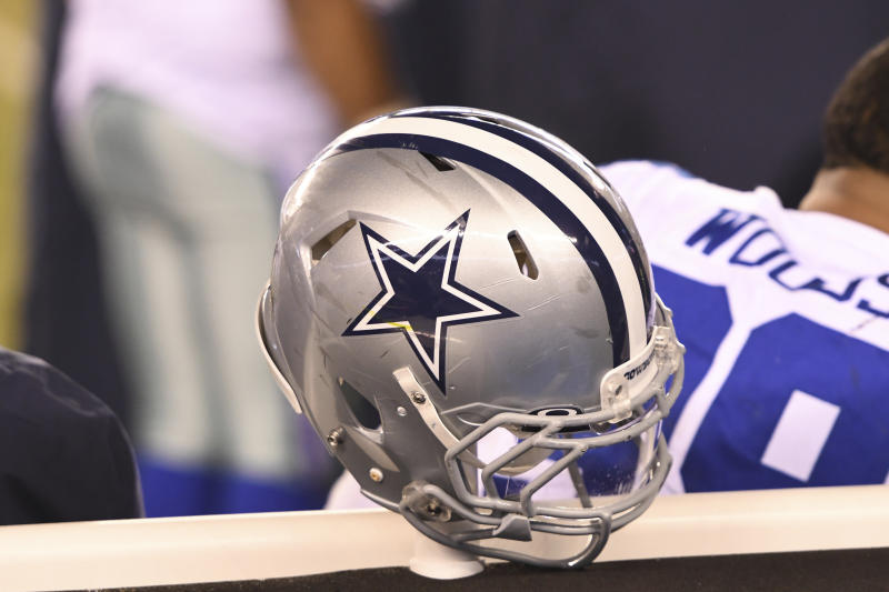 A Dallas Cowboys helmet sits on a post in the bench area during a game.