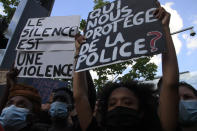 """People protest with posters reading """"Silence is violence"""" and """"Who protects us from police"""" outside the Palace of Justice Tuesday, June 2, 2020 in Paris. French authorities banned the protest over racial injustice and heavy-handed police tactics as global outrage over what happened to George Floyd in the United States kindled frustrations across borders and continents. Family and friends of Adama Traore, a French black man who died shortly after he was arrested by police in 2016, call for a protest which will also pay homage to George Floyd. (AP Photo/Michel Euler)"""