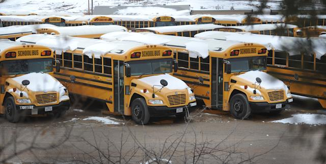 Rows of snow-covered school buses sat idle in their parking lot as the Wichita Falls, Texas, Independent School District declared Monday, Feb. 3, 2014, an Inclement Weather Day in Wichita Falls. The city received 4 inches officially, with some areas of North Texas getting more than 12 inches of snow. (AP Photo/Wichita Falls Times Record News, Torin Halsey)