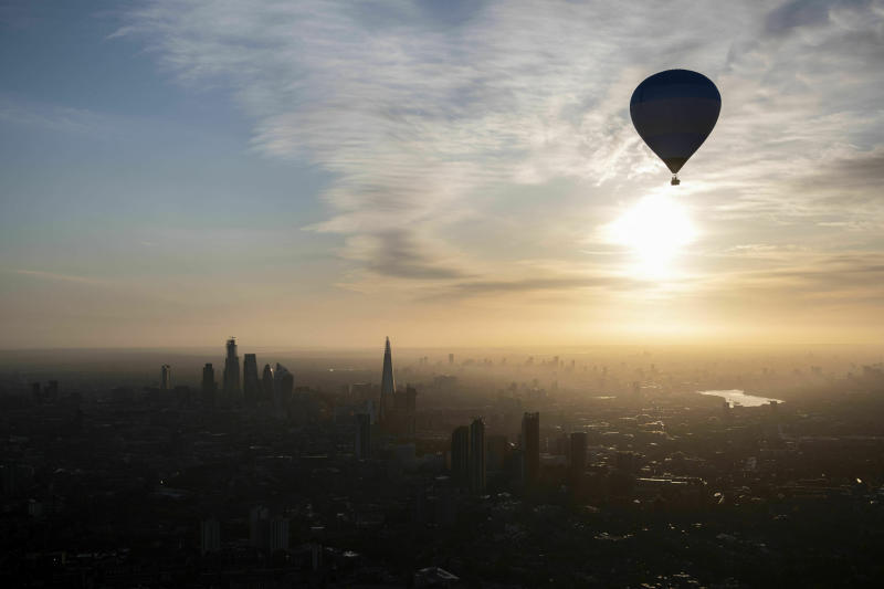 A hot air balloon flies over the London skyline during the 2019 Lord Mayor's Hot Air Balloon Regatta early Sunday June 9, 2019. (David Mirzoeff/PA via AP)