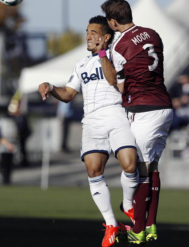 Vancouver Whitecaps forward Camilo Sanvezzo, left, collides with Colorado Rapids defenseman Drew Moor while pursuing the ball in the first half of a MLS soccer game in Commerce City, Colo., on Saturday, Oct. 19, 2013. (AP Photo/David Zalubowski)
