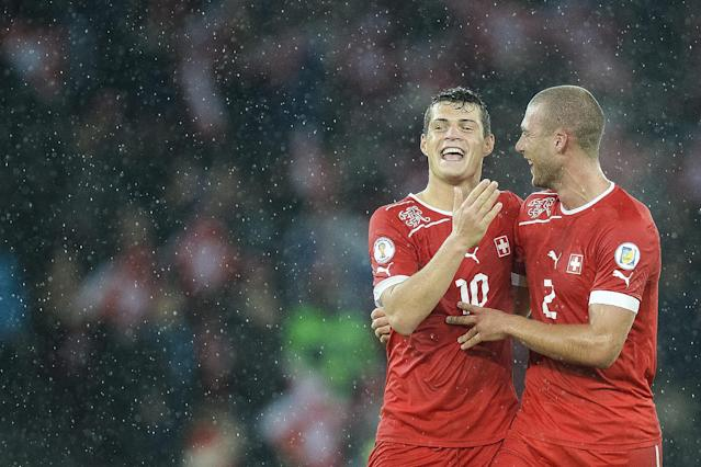 FILE - In this October 15, 2013, file photo, Switzerland's Granit Xhaka, left, and Switzerland's Pajtim Kasami, right, celebrate after winning the FIFA World Cup 2014 group E qualifying soccer match between Switzerland and Slovenia at the Stade de Suisse stadium in Bern, Switzerland. (AP Photo/Keystone/Jean-Christophe Bott)