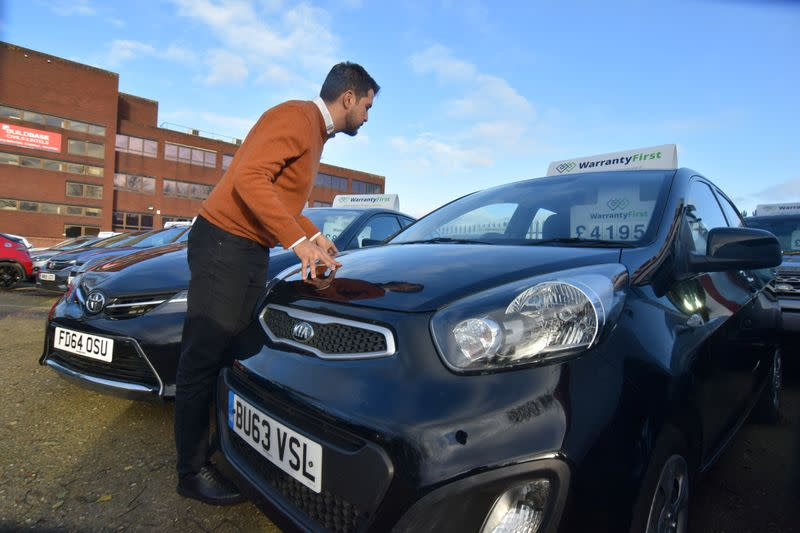 Ameen Sultani looks inside a car as he shows some of the older, cheaper vehicles that have been popular with customers eager to avoid public transport during the coronavirus disease (COVID-19) pandemic, in Hayes