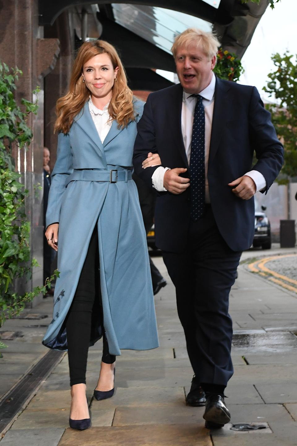 """For the first day of the Conservative Party Conference in Manchester, Carrie Symonds opted for a Tory blue woolen coat by British designer Isabelle Fox, which costs £475. The eco-friendly coat is made from English wool and doesn't contain any microplastics or polyester. She styled the trench coat with a pair of black trousers, a white blouse and black court shoes. <a href=""""https://fave.co/3339MGE"""" rel=""""nofollow noopener"""" target=""""_blank"""" data-ylk=""""slk:Shop now"""" class=""""link rapid-noclick-resp"""">Shop now</a>. <em>[Photo: Getty Images]</em>"""
