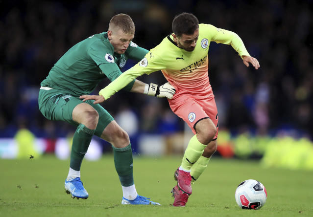 Everton goalkeeper Jordan Pickford, left, and Manchester City's Bernardo Silva in close action during their English Premier League soccer match at Goodison Park in Liverpool, England, Saturday Sept. 28, 2019. (Peter Byrne/PA via AP)