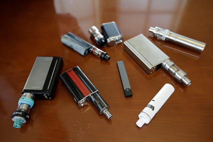 FILE - This Tuesday, April 10, 2018 file photo shows vaping devices, including a Juul, center, that were confiscated from students at a high school in Marshfield, Mass. (AP Photo/Steven Senne, File) ORG XMIT: MASR201