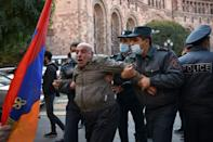 Armenian police officers detain a protester near the government headquarters.