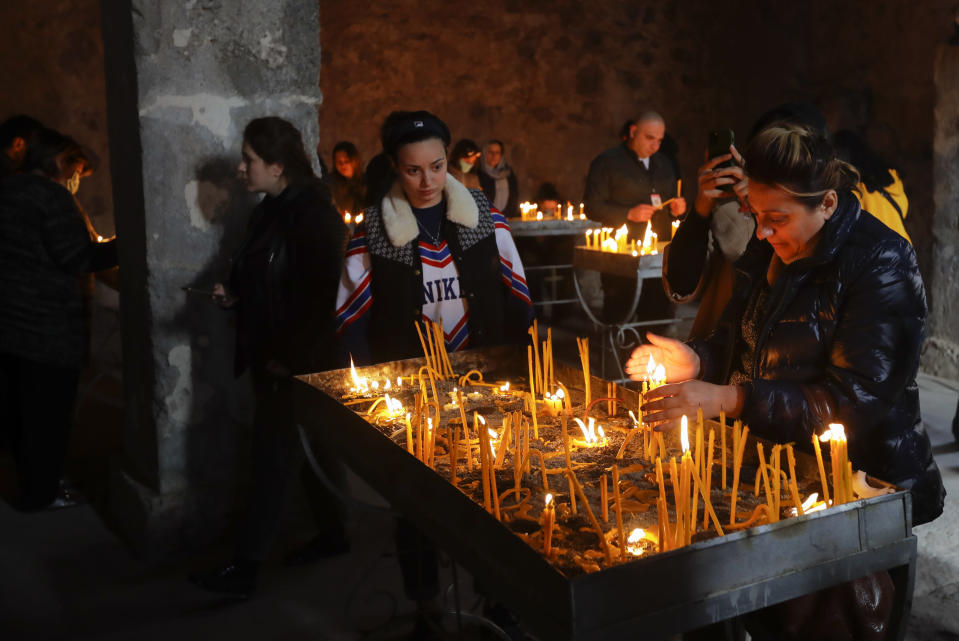 Armenians light candles while visiting the 12th-13th century Orthodox Dadivank Monastery on the outskirts of Kalbajar, the separatist region of Nagorno-Karabakh, on Friday, Nov. 13, 2020. Under an agreement ending weeks of intense fighting over Nagorno-Karabakh, some Armenian-held territories, such as this area, will pass to Azerbaijan. (AP Photo/Sergei Grits)