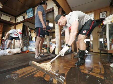 Canada's rugby player Nelson helps remove mud inside a house at a flooded area, caused by Typhoon Hagibis in Kamaishi