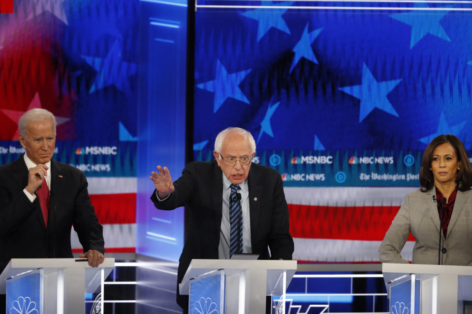 Democratic presidential candidate Sen. Bernie Sanders, I-Vt., speaks as former Vice President Joe Biden and Sen. Kamala Harris, D-Calif., listen during a Democratic presidential primary debate, Wednesday, Nov. 20, 2019, in Atlanta. (AP Photo/John Bazemore)