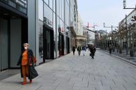 FILE PHOTO: A woman wearing a protective mask walks downtown in Frankfurt, Germany, in March 2020