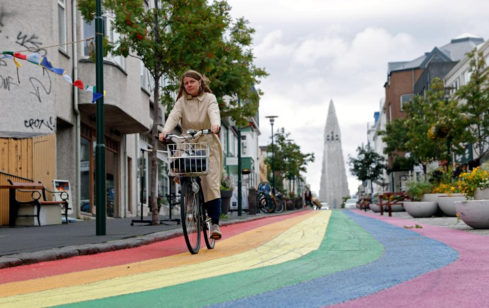 A woman cycles down a street painted in rainbow colours near the Hallgrimskirkja church, in Reykjavik, Iceland. The world's largest trial of a four-day working week in Iceland proved a success. Photo: John Sibley/Reuters