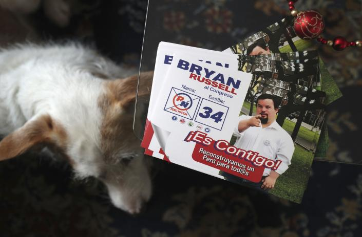 """In this Dec. 13, 2019 photo, campaign materials for congressional candidate Bryan Russell sit on a table at his home during an interview in Lima, Peru. """"I'm someone clean, honest, transparent,"""" Russell said during the interview, while sitting next to Amor, a pet dog he rescued from the street. (AP Photo/Martin Mejia)"""