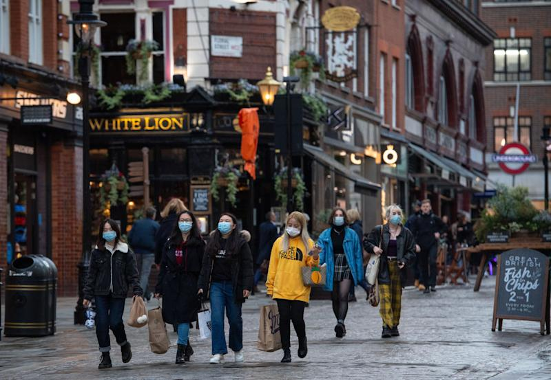 People wearing face masks in Covent Garden, in central London.