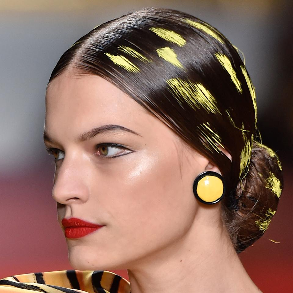 Sleek, low buns at Moschino were spotted with strokes of paint by hairstylist Julien d'Ys to coordinate with the abstract art theme of the spring/summer 2020 show. Makeup artist Kabuki lined the outer corners of the models' eyes with MAC's soon-to-be-released Dual Dare All-Day Waterproof Liner and painted their lips scarlet red.