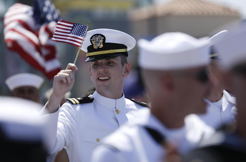 A sailor waves a flag during the gay pride parade Saturday, July 21, 2012, in San Diego. For the first time ever, U.S. service members marched in a gay pride event decked out in uniform Saturday, after a recent memorandum from the Defense Department to all military branches made an allowance for the San Diego parade - even though its policy generally bars troops from marching in uniform in parades. (AP Photo/Gregory Bull)