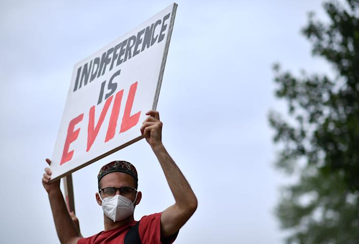 """<i>Protester holds a sign that says """"Indifference is evil"""" during an anti-racism demonstration in London on June 3. </i>"""