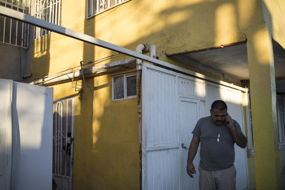 Alex Varela talks on his phone on Nov. 28, 2018, after taking a woman and her three children to his relative's home in Juarez,. (Photo: Adria Malcolm for Yahoo News)