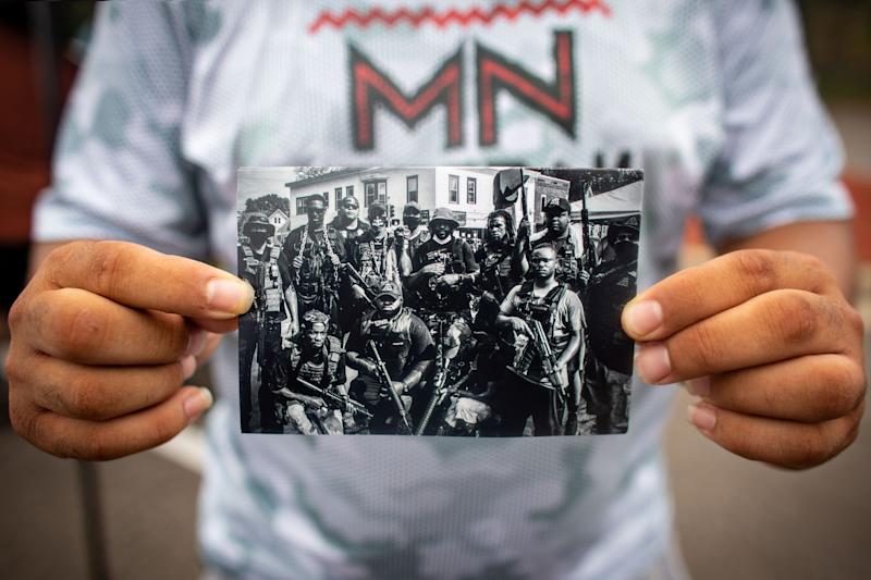 Romeal Taylor holds a photo of the Minnesota Freedom Fighters outside Cup Foods, where George Floyd died.