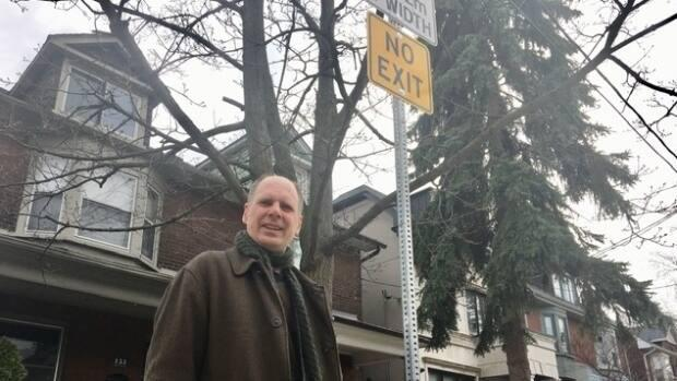 Walk Toronto co-founder Dylan Reid stands by a 'No Exit' sign on a Riverdale street that actually does have an exit — if you're a pedestrian. (Mike Smee/CBC - image credit)