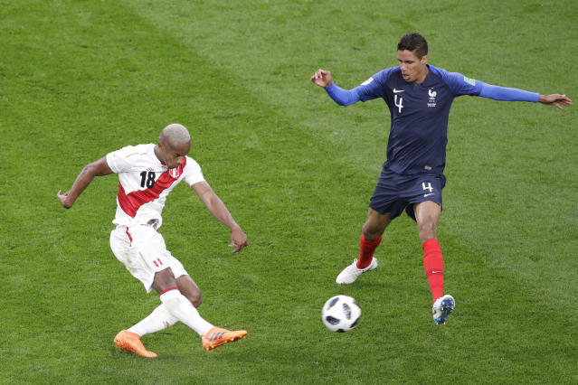 Peru's Andre Carrillo, left, kicks past France's Raphael Varane during the group C match between France and Peru at the 2018 soccer World Cup in the Yekaterinburg Arena in Yekaterinburg, Russia, Thursday, June 21, 2018. (AP Photo/Mark Baker)