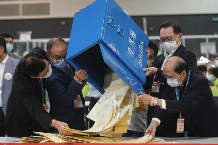 Erick Tsang, second left, Secretary for Constitutional and Mainland Affairs Bureau, helps officials pour out ballots from a box at a counting center in Hong Kong, Sunday, Sept. 19, 2021. Select Hong Kong residents voted for members of the Election Committee that will choose the city's leader in the first polls Sunday following reforms meant to ensure candidates with Beijing loyalty. (AP Photo/Vincent Yu)