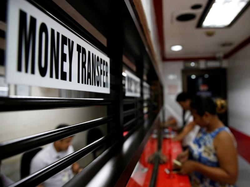 FILE PHOTO: Customers receive money from families working abroad at a money remittance center in Makati