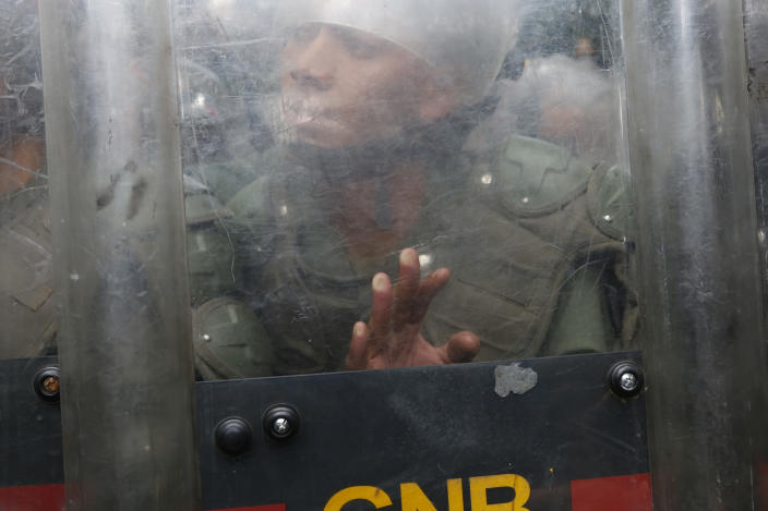 A National Guard soldier pushes his shield against members of the press and opposition lawmakers inside the grounds of the National Assembly in Caracas, Venezuela, Tuesday, Jan. 7, 2020. Venezuelan opposition leader Juan Guaidó and lawmakers who back him pushed their way into the legislative building on Tuesday following an attempt by rival legislators to take control of the congress. (AP Photo/Andrea Hernandez Briceño)