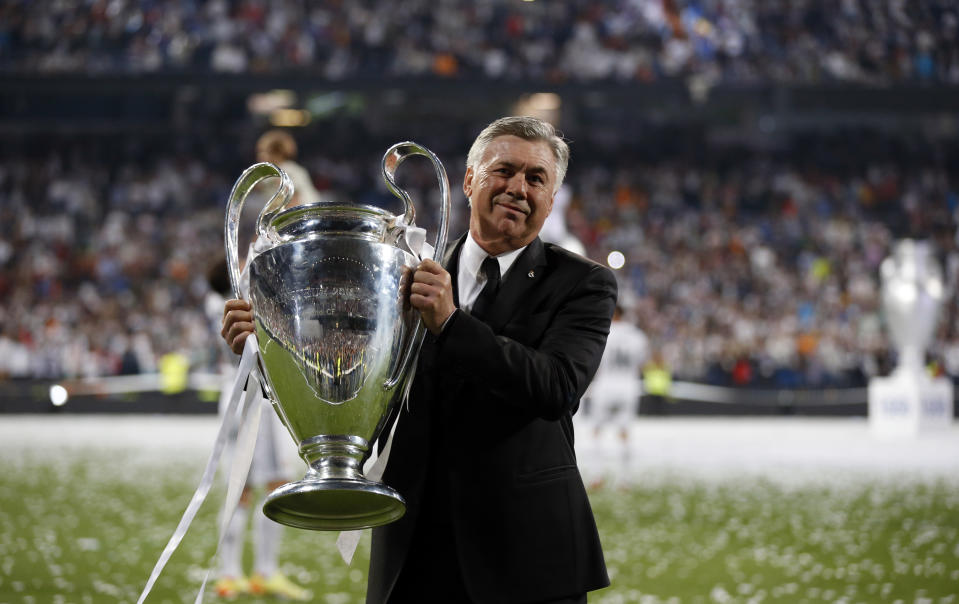 Real Madrid's coach Carlo Ancelotti poses with  the Champions League trophy during a victory ceremony at Santiago Bernabeu stadium in Madrid May 25, 2014. Real Madrid won its 10th Champions League title after beating Atletico Madrid in the final match in Lisbon.    REUTERS/Paul Hanna (SPAIN  - Tags: SPORT SOCCER)
