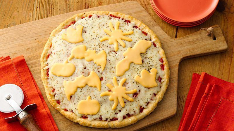 """<p>This pizza recipe is perfect for the family this holiday. You can make the pizza dough using a <a href=""""https://www.thedailymeal.com/cook/10-things-you-didn-t-know-you-could-make-bisquick-slideshow?referrer=yahoo&category=beauty_food&include_utm=1&utm_medium=referral&utm_source=yahoo&utm_campaign=feed"""" rel=""""nofollow noopener"""" target=""""_blank"""" data-ylk=""""slk:biscuit mix"""" class=""""link rapid-noclick-resp"""">biscuit mix</a>, then break out the cookie cutters to cut cheese slices in the shapes of bats, pumpkins and spiders to add Halloween flair.</p> <p><a href=""""https://www.thedailymeal.com/recipe/pizza-cheese-halloween?referrer=yahoo&category=beauty_food&include_utm=1&utm_medium=referral&utm_source=yahoo&utm_campaign=feed"""" rel=""""nofollow noopener"""" target=""""_blank"""" data-ylk=""""slk:For the Halloween Cheese Pizza recipe, click here."""" class=""""link rapid-noclick-resp"""">For the Halloween Cheese Pizza recipe, click here.</a></p>"""