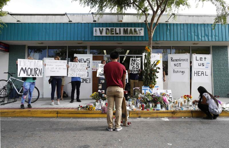 People protest the presence of news crews as a man stands in front of a makeshift shrine for 20-year-old UCSB student Christopher Michael-Martinez outside a deli that was one of nine crime scenes after series of drive-by shootings that left 7 people dead in the Isla Vista neighborhood of Santa Barbara, California May 26, 2014. Twenty-two year old Elliot Rodger killed six people before taking his own life in a rampage through a California college town shortly after he posted a threatening video railing against women, police said on Saturday. REUTERS/Lucy Nicholson (UNITED STATES - Tags: CRIME LAW CIVIL UNREST)