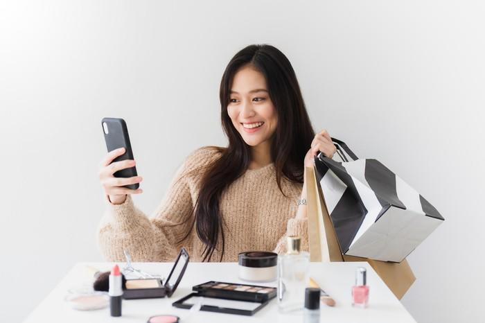 A beauty blogger streams a live video on her smartphone.