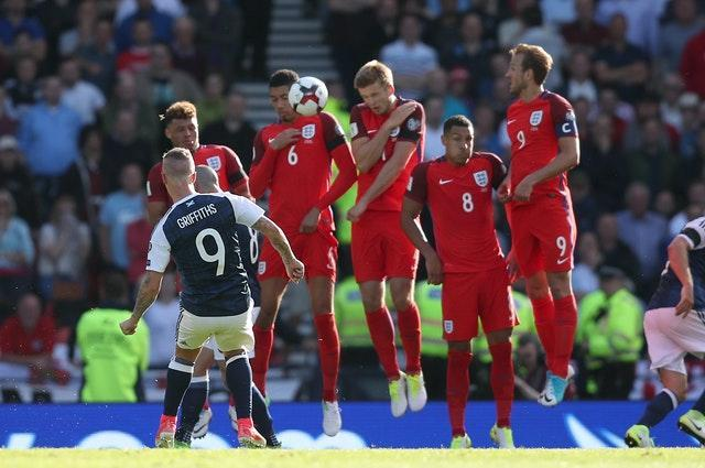 Leigh Griffiths bends his second goal of the game against England.
