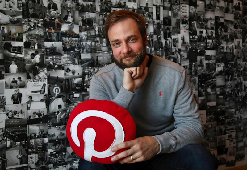 "In this Thursday, Oct. 11, 2018, photo Evan Sharp, Pinterest co-founder and chief product officer, poses for a photo in his office beside a wall of pinned photos he has taken at Pinterest headquarters in San Francisco. ""Social media is about sharing what you are doing with other people,"" said Sharp. ""Pinterest isn't about sharing. It's mostly about yourself, your dreams, your ideas you want for your future."" (AP Photo/Ben Margot)"