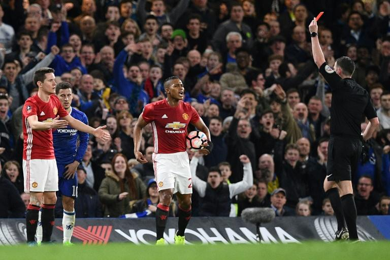 English referee Michael Oliver (R) shows a red card to Manchester United's midfielder Ander Herrera (L) during their English FA Cup match against Chelsea in London on March 13, 2017