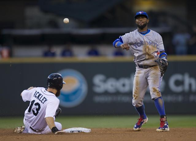 Toronto Blue Jays shortstop Jose Reyes, right, throws to first base, but is unable to turn a double play as Seattle Mariners' Dustin Ackley slides into second base during the third inning of a baseball game, Wednesday, Aug. 13, 2014, in Seattle. Ackley was ruled out on the play. (AP Photo/Stephen Brashear)