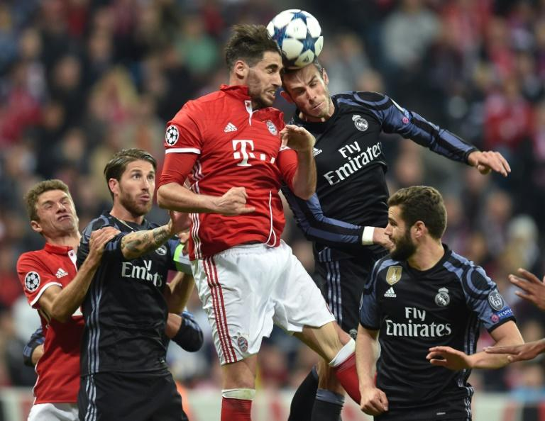 Bayern Munich's midfielder Javi Martinez (top L) and Real Madrid's midfielder Toni Kroos (top R) vie for the ball during the UEFA Champions League 1st leg quarter-final football match April 12, 2017