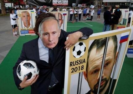 A Reporter Without Borders (RSF) activist, wearing a mask depicting Russian President Vladimir Putin, stands next to a giant portrait of journalist Alexei Kungurov on Place de la Republique, transformed into a soccer field to denounce abuse of press freedom in Russia before the start of the 2018 FIFA World Cup Russia, in Paris, France, June 13, 2018. REUTERS/Philippe Wojazer