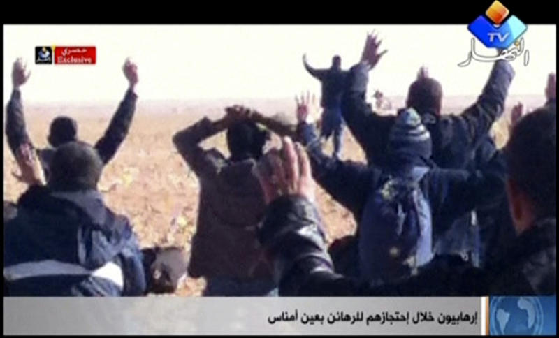 "In this image made from video, a group of people believed to be hostages kneel in the sand with their hands in the air at an unknown location in Algeria. An Algerian security official says de-mining squads searching for explosives found ""numerous"" bodies Sunday, Jan. 20, 2013 at a gas refinery where Islamic militants took dozens of foreign workers hostage. (AP Photo/Ennahar TV) ALGERIA OUT, TV OUT"