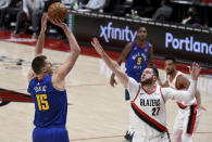 Denver Nuggets center Nikola Jokic, left, hits a shot over Portland Trail Blazers center Jusuf Nurkic (27) during the first half of an NBA basketball game in Portland, Ore., Wednesday, April 21, 2021. (AP Photo/Steve Dykes)