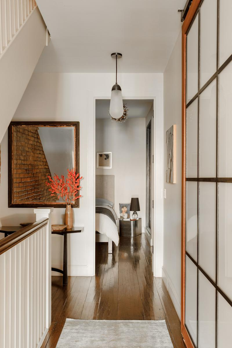 """The hallway leading to the guest bedroom initially had sliding wood doors painted the same color as the wall. """"It was boring to me,"""" says Tierney, who hired a local craftsman to create the current wood-and-glass ones that hide the washer/dryer. The black lacquer entry table, based off a Tommi Parzinger piece, was designed by Stuno."""