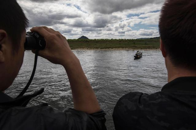 <p>Chinese tourists look at a North Korean fisherman as they ride in a boat on the Yalu river with North Korean territory on both sides north of the border city of Dandong, Liaoning province, northern China across from the city of Sinuiju, North Korea on May 23, 2017 in Dandong, China. (Photo: Kevin Frayer/Getty Images) </p>