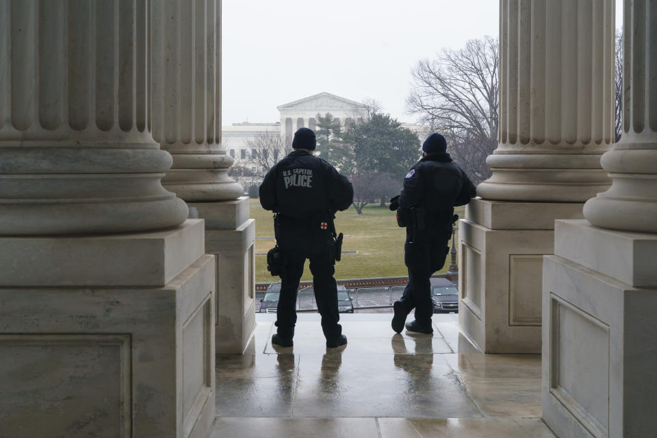 U.S. Capitol Police officers stand watch outside the Senate as lawmakers vote on procedures to proceed with the impeachment of former President Donald Trump for inciting the January 6, 2021, attack on the Capitol by pro-Trump supporters, at the Capitol in Washington, Tuesday, Jan. 26, 2021. (AP Photo/J. Scott Applewhite)